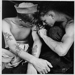 Dos marineros, uno de ellos tatuando al otro