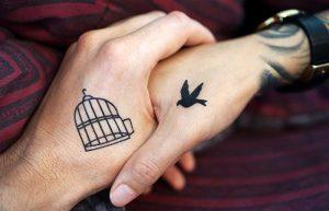 Manos de dos personas entrelazadas, una con una jaula tatuada y la otra con un pájaro tatuado simbolizando unión.