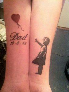 Dos antebrazos que uno lleva tatuado una niña y el otro un globo y la palabra papá junto con una fecha simbolizando el fallecimiento de su padre.